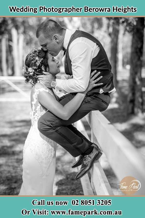 Photo of the Groom sitting on the fence while kissing the Bride on the forehead Berowra Heights NSW 2082