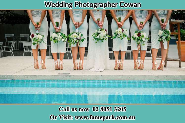 Behind photo of the Bride and the bridesmaids holding flowers near the pool Cowan NSW 2081