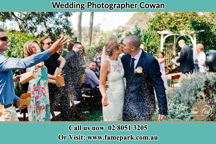 Photo of the Bride and the Groom kissing while showering rice by the visitors Cowan NSW 2081