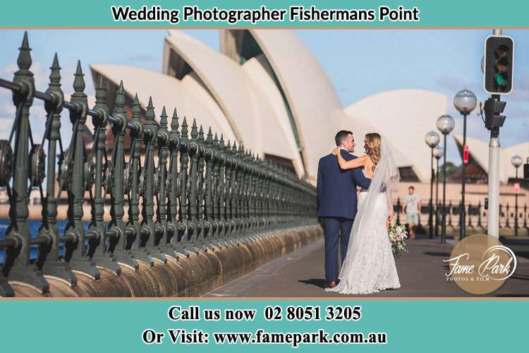 The Groom and the Bride walking towards the Sydney Grand Opera House Fishermans Point NSW 2082