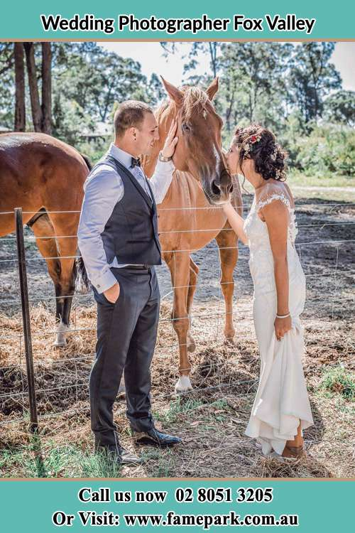 Photo of the Groom and the Bride caressing a horse Fox Valley NSW 2076