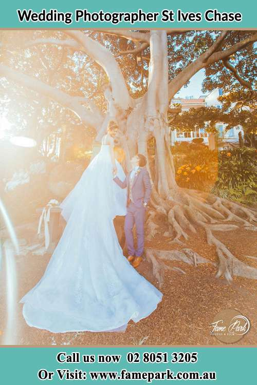 Photo of the Bride and the Groom looking each other besides the tree St Ives Chase NSW 2075