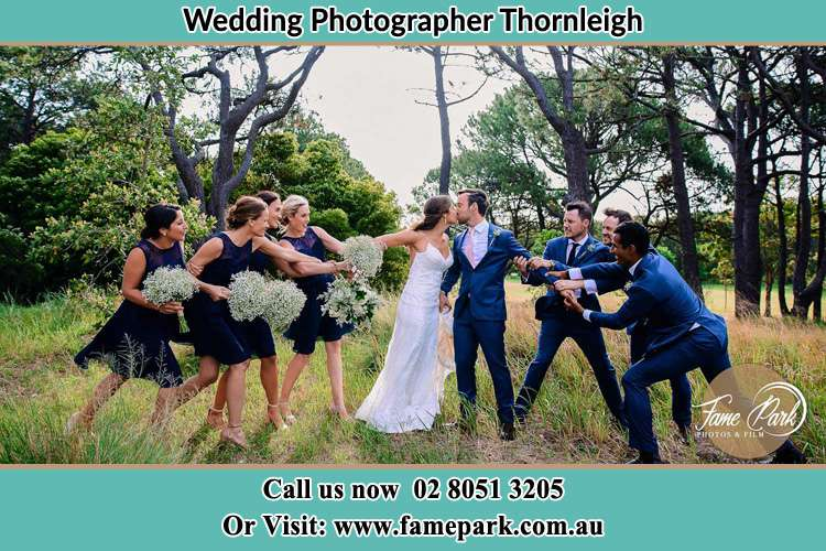 Photo of the Bride and the Groom kissing while teasing by the entourage Thornleigh NSW 2120