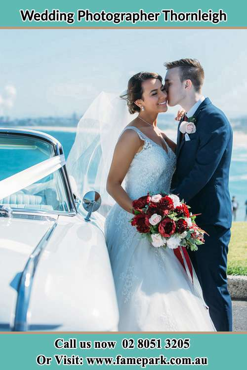 Photo of the Groom kiss the Bride besides the bridal car Thornleigh NSW 2120