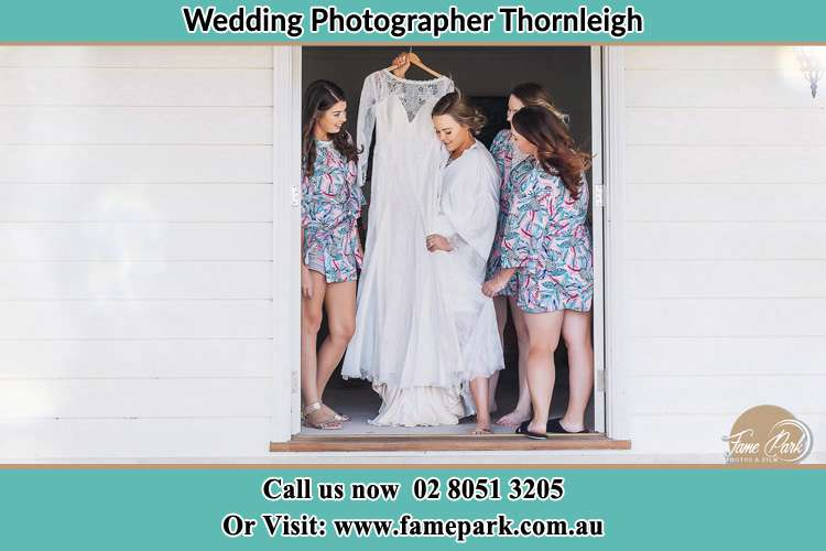 Photo of the Bride and the bridesmaids checking the wedding gown at the door Thornleigh NSW 2120
