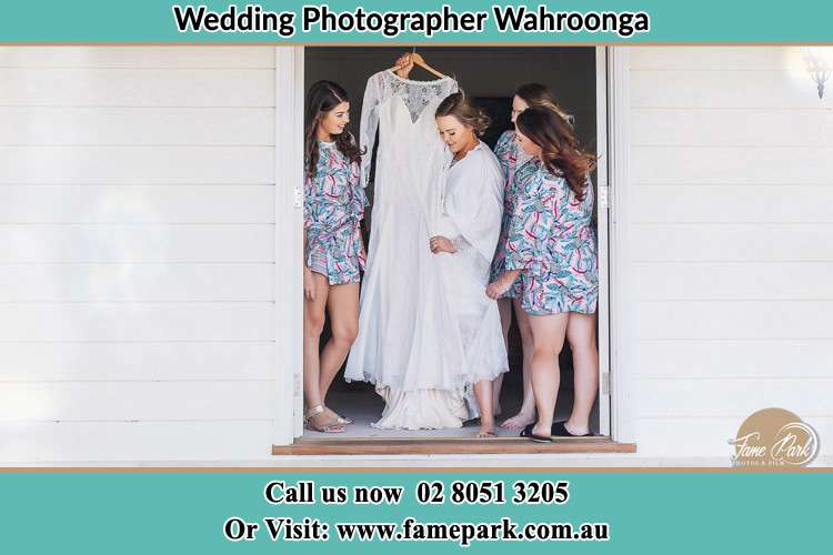 Photo of the Bride and the bridesmaids checking the wedding gown at the door Wahroonga NSW 2076
