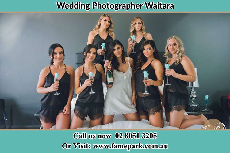 Photo of the Bride and the bridesmaids wearing lingerie and holding glass of wine on bed Waitara NSW 2077